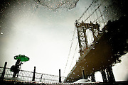 Reflection of the silhouette of a photographer shooting by the manhattan bridge on a rainy day in DUMBO, Brooklyn, New York, 2010.
