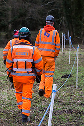 Denham, UK. 4 February, 2020. Engineers and a security guard walk across land cleared for works for the HS2 high-speed rail link project in the direction of the river Colne. Planned works in the immediate vicinity are believed to include the felling of 200 trees and the construction of a roadway, Bailey bridge, compounds, fencing and a parking area.