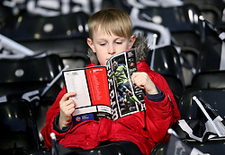 A young fan in the stands reads through the match programme