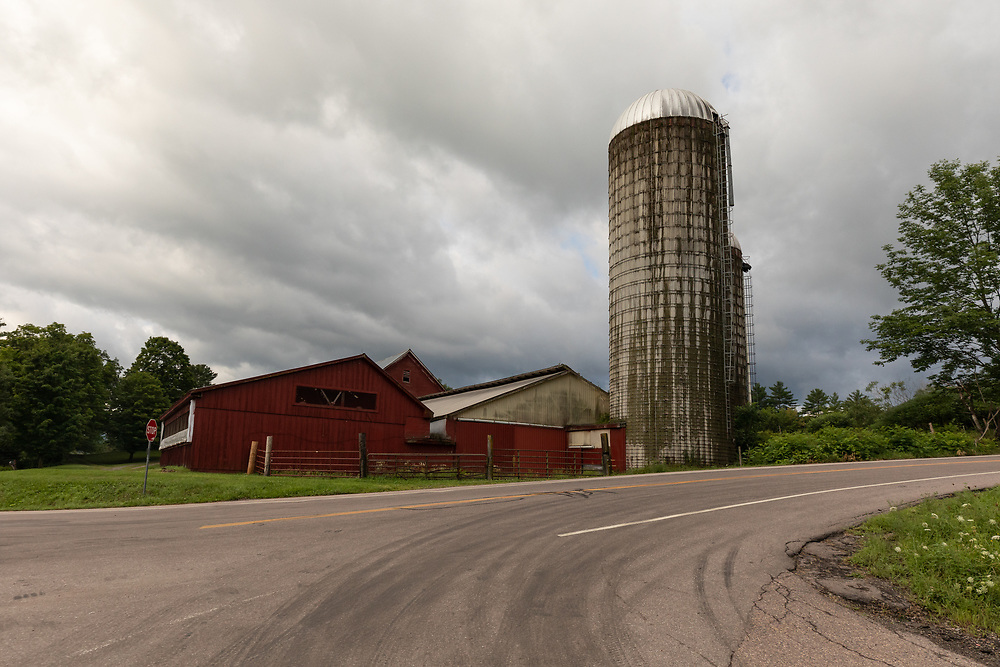 A farm silo standing tall on a stormy morning along Route 100 in Vermont.