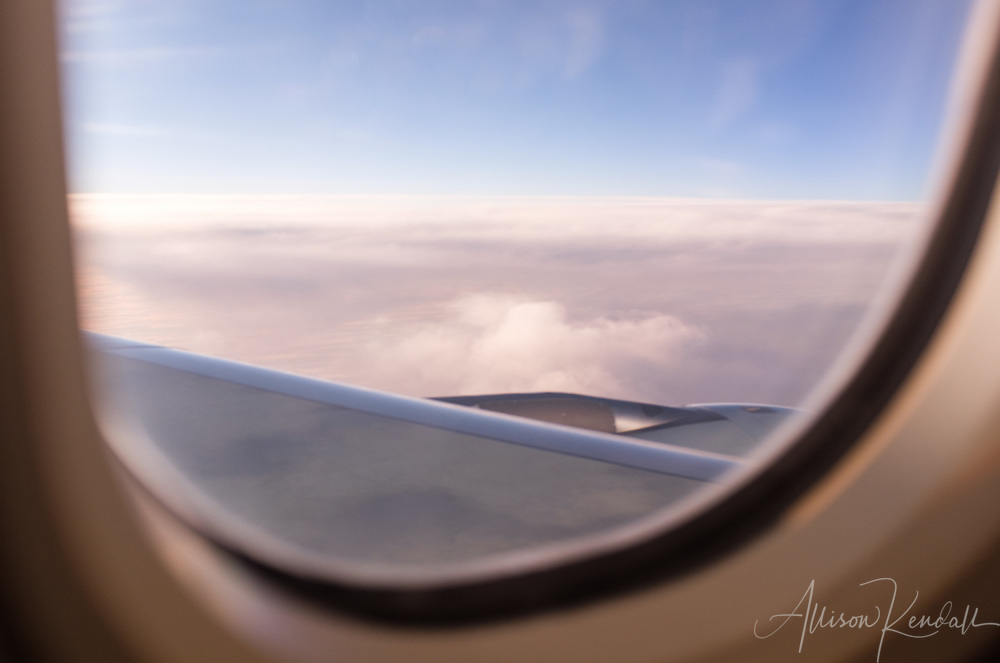Soft light and clouds, framed by an airplane window