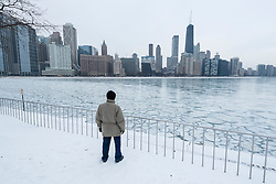 © Licensed to London News Pictures. 21/12/2016. Chicago, USA. A man takes in the view in Milton Olive Park. After several days of extremely low temperatures, a frozen Lake Michigan, off Lake Shore Drive in Chicago, is seen on the day of the winter solstice. Photo credit : Stephen Chung/LNP