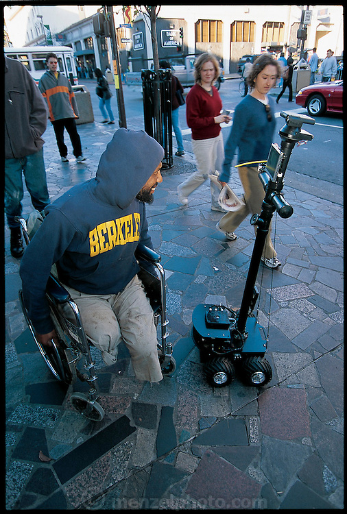 """On a test run on Telegraph Avenue, a busy retail street near the UC Berkeley campus, Paulos controls the ProP (Personal Roving Presence) from a short distance away, via a remote link. One amused man in a wheelchair even stops and asks it for a light. Berkeley graduate student Eric Paulos describes his (PRoP) as """"a simple, inexpensive, Internet-controlled, untethered tele-robot that strives to provide the sensation of tele-embodiment in a remote real space."""" Berkeley, CA. From the book Robo sapiens: Evolution of a New Species, page 169."""