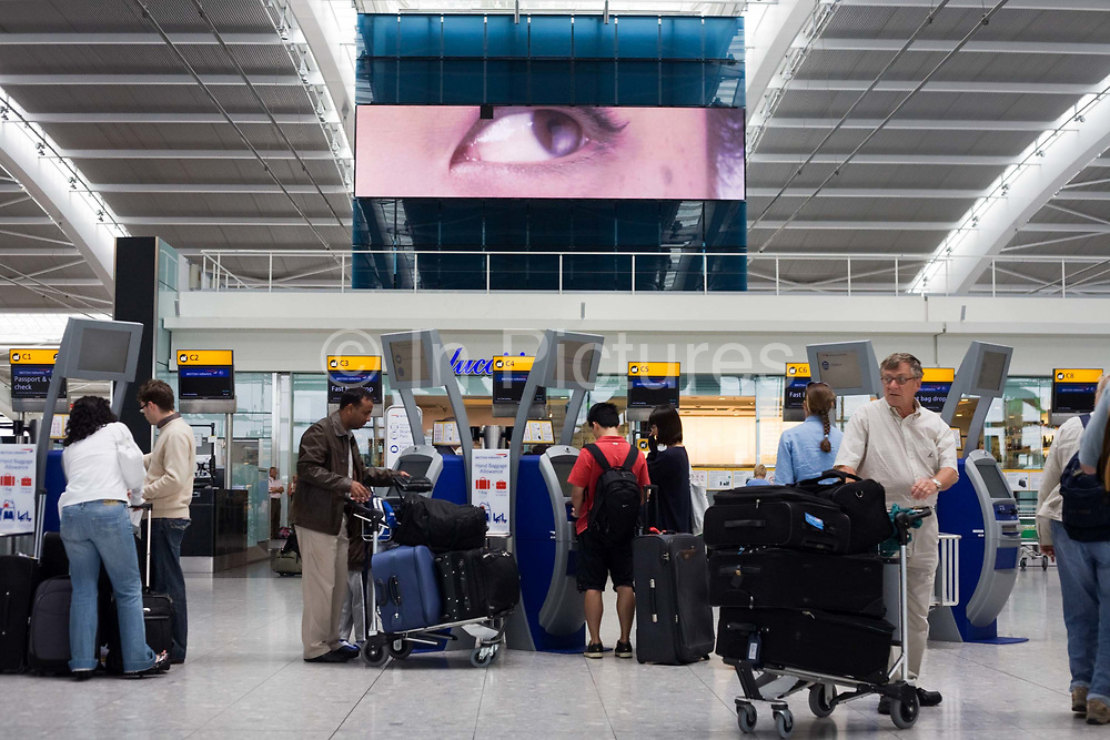 """A scene of busy modern air travel as international passengers check-in at the British Airways Heathrow Airport's Terminal 5. Under the gaze of a giant eye that seems to be peering from out of a massive TV screen, the self-service kiosks that have been developed to allow customers to process their own ticketing on arrival at this aviation hub for British Airways. Once they've chosen their seat and printed a boarding pass, they can go straight to the Fast Bag Drop desk at the airport. There, baggage will be tagged by an agent and sent to the aircraft. At a cost of £4.3 billion, Terminal 5 has the capacity to serve around 30 million passengers a year. From writer Alain de Botton's book project """"A Week at the Airport: A Heathrow Diary"""" (2009)."""