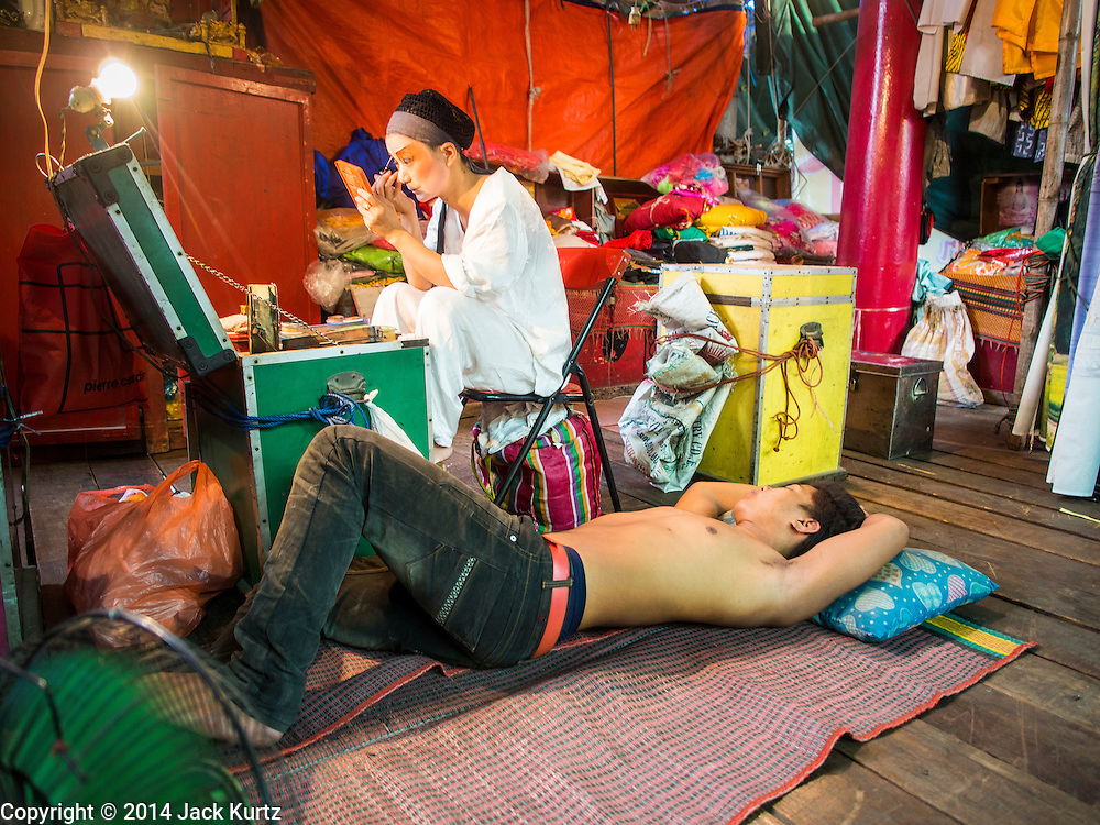 23 SEPTEMBER 2014 - BANGKOK, THAILAND: A performer at the Chinese opera puts on her makeup while a member of the crew naps on stage on the first day of the Vegetarian Festival at the Chit Sia Ma Chinese shrine in Bangkok. The Vegetarian Festival is celebrated throughout Thailand. It is the Thai version of the The Nine Emperor Gods Festival, a nine-day Taoist celebration beginning on the eve of 9th lunar month of the Chinese calendar. During a period of nine days, those who are participating in the festival dress all in white and abstain from eating meat, poultry, seafood, and dairy products. Vendors and proprietors of restaurants indicate that vegetarian food is for sale by putting a yellow flag out with Thai characters for meatless written on it in red.    PHOTO BY JACK KURTZ