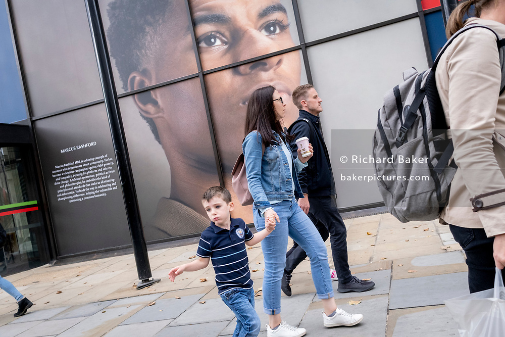 A young boy and some adults walk beneath the large billboard, a portrait of English football player, Marcus Rashford, outsidee the Strand branch of Coutts Bank, on 14th October, 2021, in Westminster, London, England. Marcus Rashford has recently been awarded an honourary degree by The University of Manchester in recognition of his political campaigning on behalf of the underprivilged (in particular, of school meals) and his philanthropy. He currently plays for Manchester United and is in the English national team. He has also been the victim of online racial abuse.