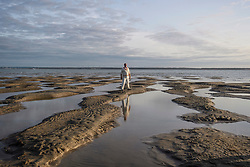 © Licensed to London News Pictures. 24/08/2017. Solent, UK.A fielder stands amongst puddles of sea water at low tide.  Teams take part in the Brambles Bank Cricket Match in the middle of The Solent strait on August 24, 2017. The annual cricket match between the Royal Southern Yacht Club and The Island Sailing Club, takes place on a sandbank which appears for 30 minutes at lowest tide. The game lasts until the tide returns. Photo credit: Ben Cawthra/LNP
