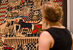© Licensed to London News Pictures. 08/06/2014. London, UK. A woman looks at an intricately designed quilt made by soldiers from uniforms from the Crimean War at the British Folk Art exhibition at Tate Britain in Millbank, London on 8th June 2014. The British Folk Art exhibition at Tate Britain opens on 10th June 2014 and runs until 31st August 2014. Photo credit : Vickie Flores/LNP