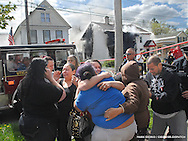 Loved ones mourn near the scene of a fatal fire Monday in Utica. A mother and three children died in the mid-morning blaze that quickly swept through 935 Schuyler Street.