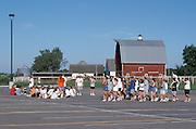 Teenagers practicing in groups in school parking lot.