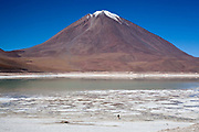 Snow capped volcano and lagoon with a person looking at them, dwarfed by their size. Salar Uyuni salt flats and Eduardo Avaroa national park, south western Bolivia