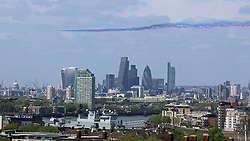 © Licensed to London News Pictures. 10/05/2015.  Today's VE Day anniversary flypast over London as seen from Greenwich. The Red Arrows were seen swooping over London leaving a plume of coloured smoke. Pictured: London vista including Tower Bridge, St Paul's, and City of London skyscape with Red Arrows overhead. Credit : Rob Powell/LNP