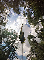 Aerial view of a person crossing the forest through a large zip line cable in Slovenia.