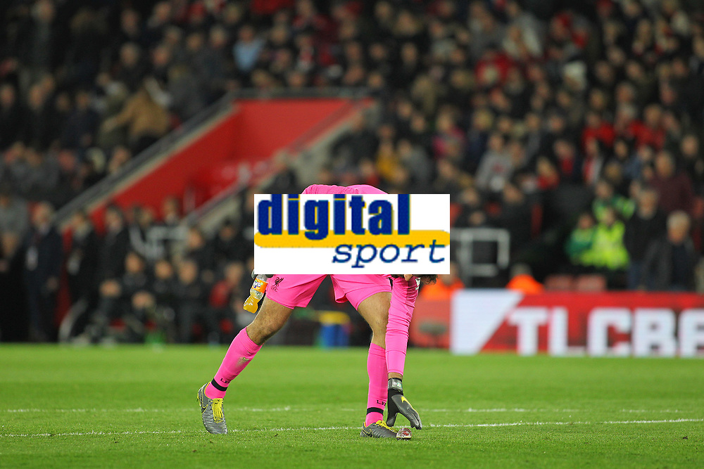 Football - 2018 / 2019 Premier League - Southampton vs. Liverpool<br /> <br /> Alisson of Liverpool picks up the two bottles thrown onto the pitch after Liverpool scored there third goal at St Mary's Stadium Southampton<br /> <br /> COLORSPORT/SHAUN BOGGUST