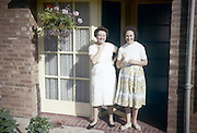 Two 1960s housewives and mothers stand in sunshine on the front porch of a council house.