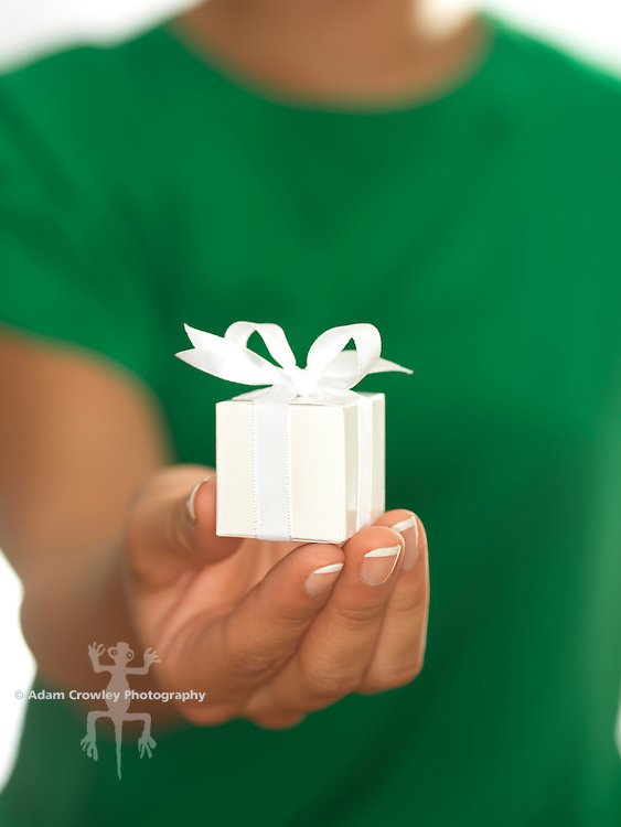 Close up of a small, white gift box  wrapped with white ribbon, held by a woman (20-30).