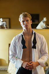 All American blond man at home in an open tuxedo shirt and bowtie