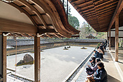 Ryoanji Temple zen garden in Kyoto with sunshine while it rains