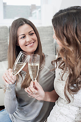 Two young women toasting with champagne glasses