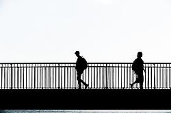 The silhouette of people walking across the Louisa Gap Bridge in Broadstairs, Kent.