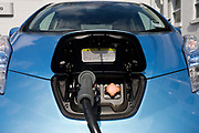 Fast charging a Nissan Leaf electric car at an electrical charging point offering an EV 30 minute charge at a south London Nissan dealership. The Nissan Leaf (Leading, Environmentally Friendly, Affordable, Family) is a five-door hatchback electric Nissan car. Its official range is 117 kilometres with an energy consumption of 765 kilojoules per kilometre and rated the Leaf's combined fuel economy at 2.4 L/100 km.