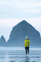 Image of young woman running on the beach in Cannon Beach, Oregon.