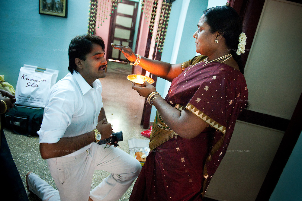 prior to his wedding in Madurai, the groom's mother blesses him before going to the wedding venue for the prayer ceremony