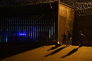 Migrants are pictured by the United States border wall after crossing the border from Ciudad Juárez, Mexico, heading to El Paso, Texas, U.S., on February 11, 2021. Photographer Paul Ratje/Bloomberg