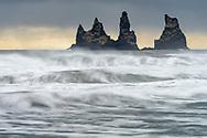 """Die imposanten Felsnadeln an der Küste bei der Ortschaft Vík. Die ganze Gruppe heisst Reynisdrangar, die einzelnen Nadeln """"Skessudrangur"""", """"Landdrangur"""" und """"Langsamur"""". Die Legende berichtet, dass Trolle ein Schiff ans Land bringen wollten und dabei versteinert worden seien."""