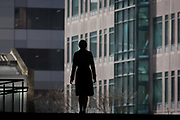 The single silhouette of woman walking through the Broadgate corporate offices development in the City of London. With both hands at her side, the lone female makes her way towards offices and corporate buildings, a backdrop of the Broadgate development within the ancient boundary of the capital's Square Mile, it's financial district founded by the Romans in AD43.