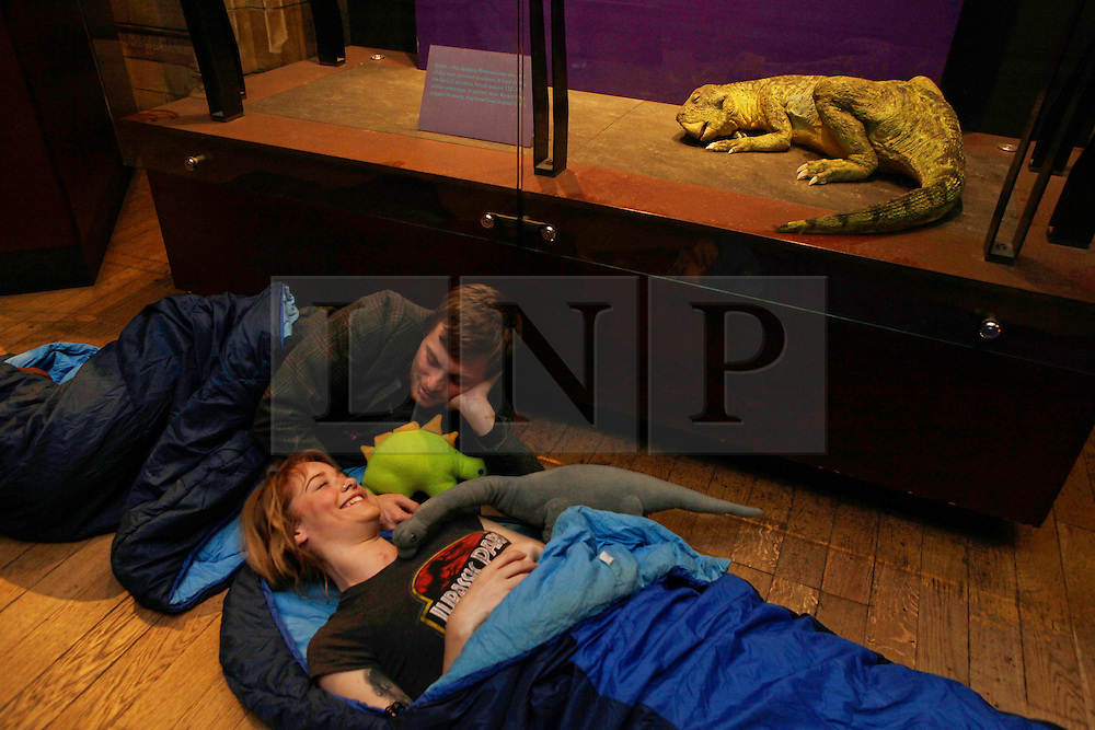 Natural History Museum, London, UK. 17/01/2014<br /> Indi Heath and Howard Sivills, from London, settle down for the night by a dinosaur exhibit in the Natural History Museum in London. The 'Dino Snore' sleepover event allowed paying adults to spend the night inside the museum, where people could sleep among the dinosaur exhibits along with activities such as eating edible bugs and a lecture on the sex lives of insects.<br /> Photo: Anna Branthwaite/LNP
