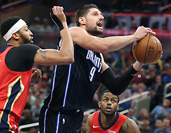 December 22, 2017 - Orlando, FL, USA - The Orlando Magic's Nikola Vucevic (9) drives past the New Orleans Pelicans' Anthony Davis, left, at the Amway Center in Orlando, Fla., on Friday, Dec. 22, 2017. (Credit Image: © Stephen M. Dowell/TNS via ZUMA Wire)
