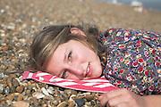 Model released teenage girl wearing floral dress lies on shingle beach