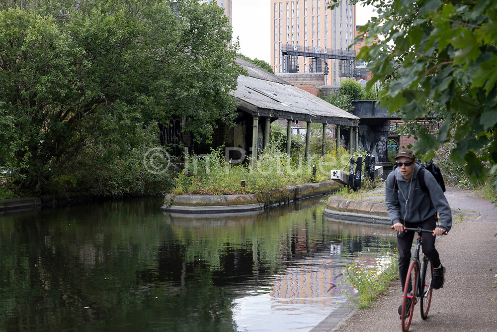 Scene along the Grand Union Canal, very close to the city centre where old, crumbling buildings provide a foreground to a modern city on 3rd August 2020 in Birmingham, United Kingdom. Birmingham has around 35 miles of canals, said to be more than in Venice, and are very much a reminder of a Birminghams industrial heritage. During the Industrial Revolution these canals were busy, transporting heavy goods like coal, iron, while playing a pivotal role in the development of Birmingham as an industrial powerhouse.