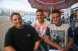 Group of young men sitting at table in street café on the seafront at Las Palmas; Gran Canaria; Canary Islands,