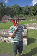 Chedworth Roman villa, near Cirencester, Gloucestershire, England. Teenage boy listens to audio tour on handset (Model Release)