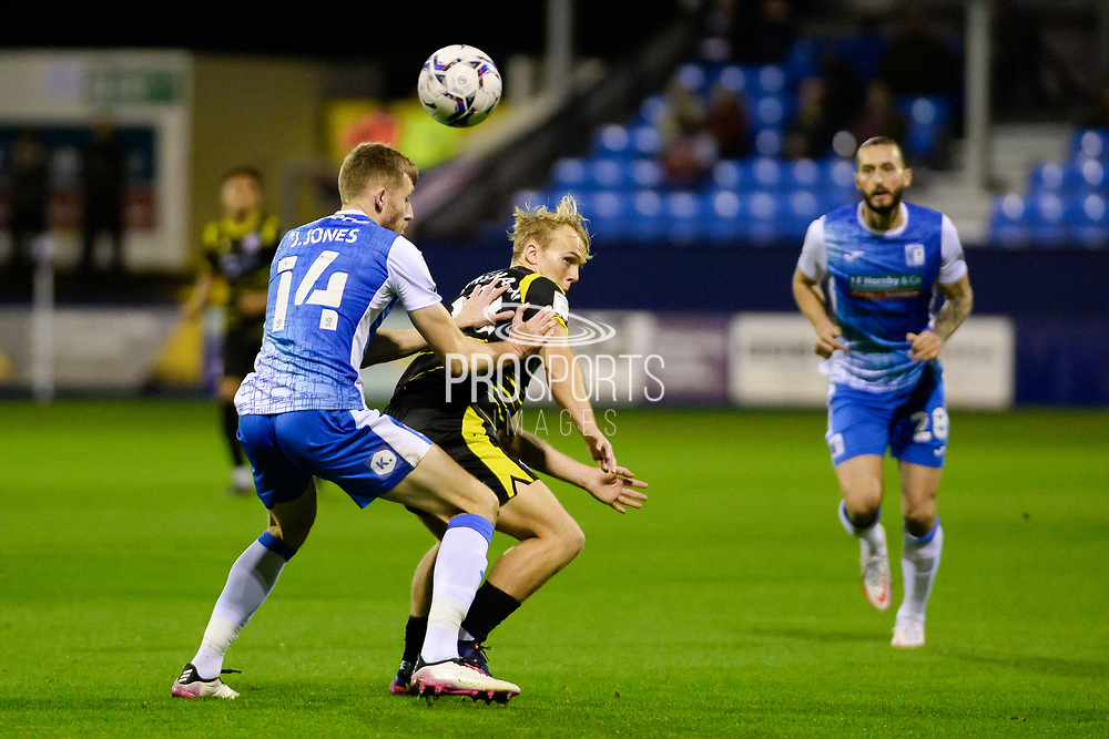 Barrow James Jones (14) Scunthorpe United Jake Scrimshaw (18) battles for possession during the EFL Sky Bet League 2 match between Barrow and Scunthorpe United at Progression Solicitors Stadium, Barrow, United Kingdom on 19 October 2021.