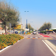 Typical road in Sottomarina Chioggia. City street with cars, campings, shops, buildings.
