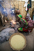 Behind a courtyard wall of stacked and dried millet stalks, Khadidja Baradine begins her morning by scooping an ember from the previous night's fire onto a handful of straw. When the straw begins to smoulder, she blows on it to start a cooking fire. Hungry Planet: What the World Eats (p. 72).