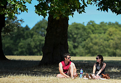 © Licensed to London News Pictures. 01/08/2018. LONDON, UK.  A couple enjoy the warm weather in Hyde Park.  Temperatures are forecast to increase back to the 30s in time for the weekend  Photo credit: Stephen Chung/LNP