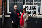Labour party leader Jeremy Corbyn and his wife Laura Alvarez stand outside a polling station in London, United Kingdom on 12th December, 2019.The election ballot papers will be counted through the night and the result is expected in the early hours of Friday morning.