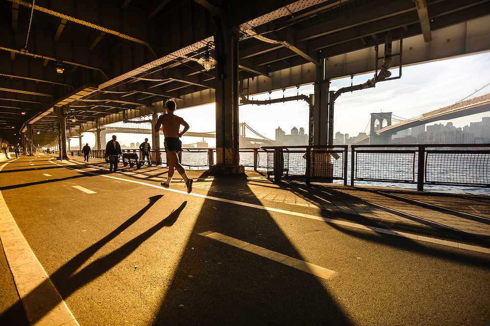 Runners and passersby down the FDR Driveway in Downtown Mahttan at sunrise, New York