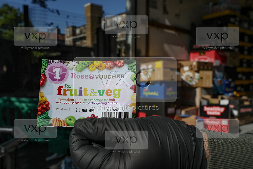 "A Kurdish local street market retailer shows voucher for fruit and veg worth of £1 collected from his customers in ""East Street Market"" in Walworth, South London on Tuesday, May 5, 2020. Under a government scheme, families in need in England should receive vouchers worth £15 a week per child. Whilst a few European countries relax the COVID-19 lockdown, Britain still remains under lockdown without an exit strategy yet. (Photo/Vudi Xhymshiti)"