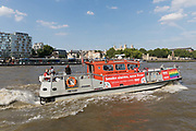 The London Fire Brigade Fire Boat, sporting London Pride flag colours sails past the Tower of London on the River Thames in London, England on July 06, 2018