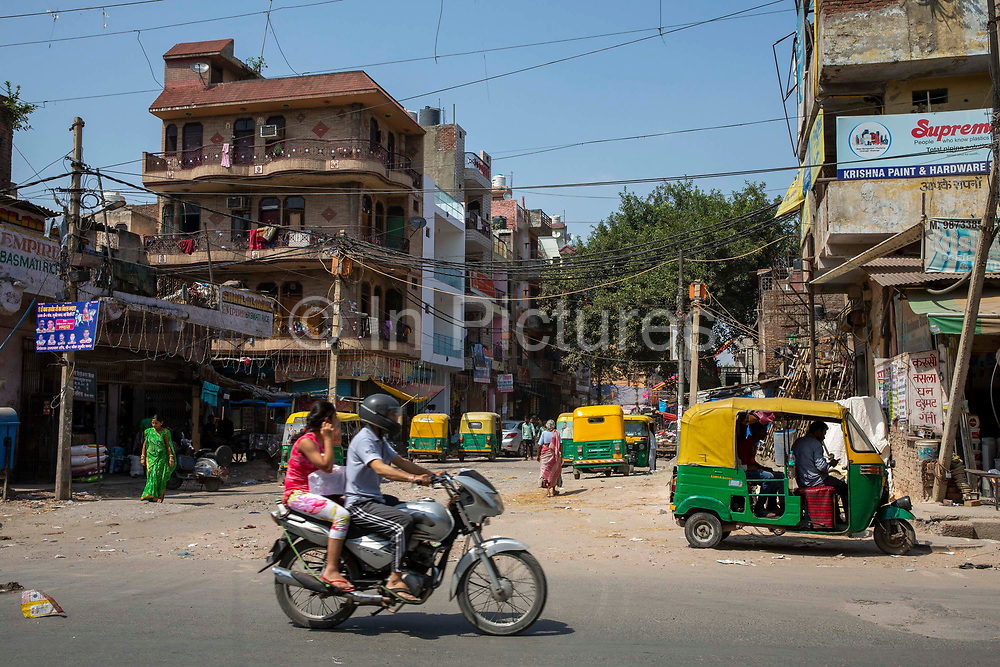 A man drives a silver motorbike carrying a woman past a typical street full with motor rickshaws on 18th September 2018 in Delhi, India.