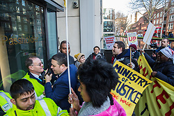 London, UK. 22nd January, 2019. Members of the United Voices of the World (UVW) trade union representing receptionists, security guards and cleaners at the Ministry of Justice (MoJ) try to rush into the entrance of the Home Office after beginning a coordinated strike for the London Living Wage of £10.55 per hour and parity of sick pay and annual leave allowance with civil servants. The strike is being coordinated with support staff at the Department for Business, Energy and Industrial Strategy (BEIS) from the Public and Commercial Services (PCS) union.
