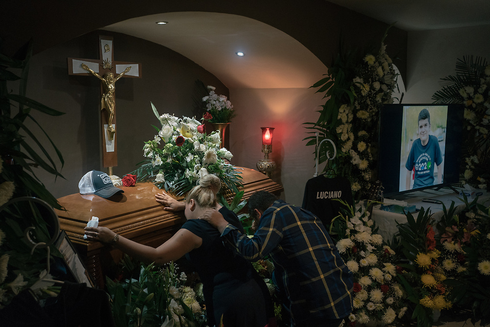 SAN FERNANDO, TAMAULIPAS, MEXICO - OCTOBER 18, 2020:  Anabel Garza Rivera,33, and Luciano Leal Vela, 38, kneel before the coffin of their murdered son surrounded by flower arrangements and his favorite clothing at a funeral home. After99 days of his kidnapping, authoritiesgot a lead from a family member that was involved and found the body of the14-year-old boy inside a suitcaseburied 22 cm deep in a field in the east part of the town.