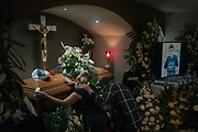 SAN FERNANDO, TAMAULIPAS, MEXICO - OCTOBER 18, 2020:  Anabel Garza Rivera,33, and Luciano Leal Vela, 38, kneel before the coffin of their murdered son surrounded by flower arrangements and his favorite clothing at a funeral home. After 99 days of his kidnapping, authorities got a lead from a family member that was involved and found the body of the 14-year-old boy inside a suitcase buried 22 cm deep in a field in the east part of the town.