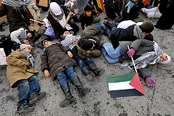 Children play dead in the street, as thousands of people protest against the Israeli air strikes on Gaza, during a demonstration in Brussels, Belgium, Sunday, Jan. 11, 2009. (Photo © Jock Fistick)