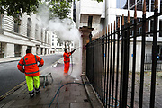 Workers clean the Conservative Party's HQ in central London after it was pelted in pink colour on Saturday, Aug 15, 2020. (VXP Photo/ Vudi Xhymshiti)